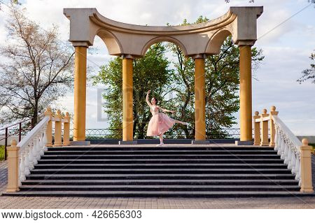 A Ballerina Dances With Her Leg Raised In An Arch Of Columns In Urban Architecture On The Embankment