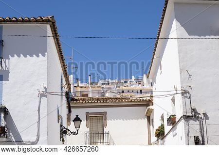 Typically Mediterranean, Whitewashed Residential Buildings And Terra Cotta Roof Tiles In Altea, Alic