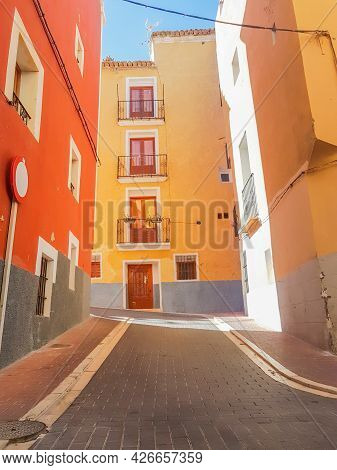 Mufti-colored Highly Decorated Homes Line Narrow Street Villa Joyosa, Alicante Spain.