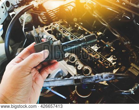 Ignition Coil For Spark Plug Of The Car Ignition System In The Mechanic Hand With A Car Engine Blurr