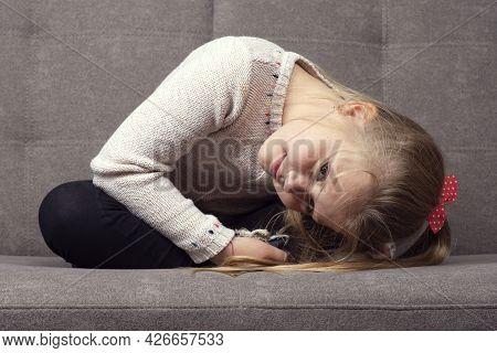 Little Caucasian Girl Sitting On A Gray Sofa.