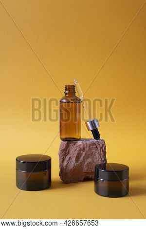 Open Amber Glass Dropper Bottle On A Piece Of Stone And Two Cream Pot. Orange Background With Daylig