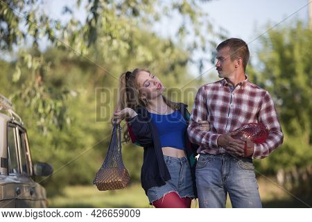 A Girl And A Guy Dressed In The Style Of The Nineties Are Holding Nets With Food And Talking.