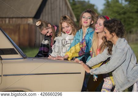 Young Cheerful Girls Are Pushing An Old Car. Women In The Style Of The 90s.