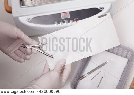 Unrecognizable Manicurist Putting Nail Nippers In Paper Envelope For Dry Heat Sterilization