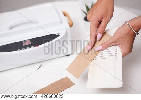 Cropped Close Up Of Manicurist Showing Paper Envelopes For Instruments Sterilization In Dry Heat Mac