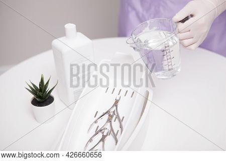 Manicurist Sterilizing Manicure Instruments With Liquid Disinfectant