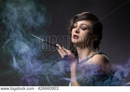 Retro Woman Portrait. Beautiful Woman In The Style Of 20s Or 30s With A Mouthpiece In Colored Smoke.