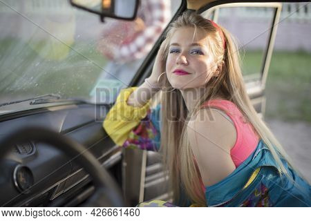 Beautiful Girls In The Style Of The 90s In Bright Clothes In The Salon Of The Car.