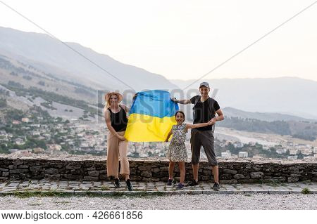 Family Of Hikers In Ukrainian With Ukrainian Flag Staying In The Mountains.