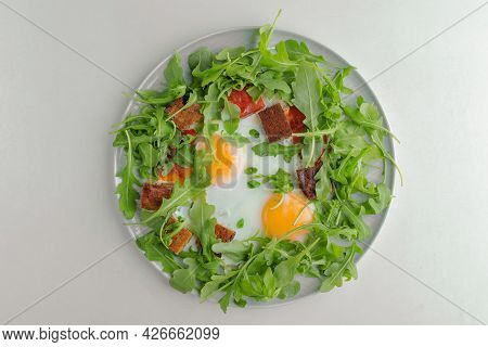 Fried Eggs With Greens And Croutons On A White Plate On A White Background