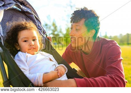 Mixed Race Family Happy Father With Little Girl In Stroller At Summer Park