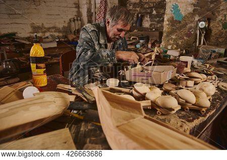 Mature Man Carpenter Making Wooden Toys In Workshop, Craftsman In Action, Old Artist At Work
