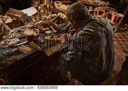 Carpenter At Work. Rear View Of An Old Craftsman Making A Wooden Model Of Sail Ship In His Home Work