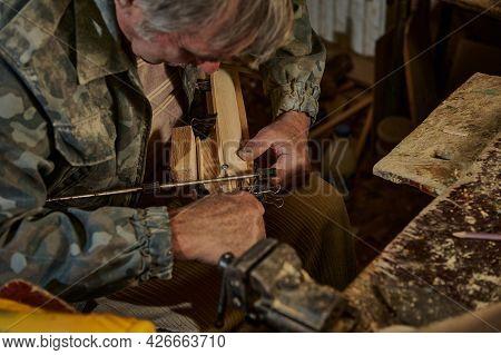 A Mature Carpenter Making A Handmade Wooden Model Of A Sailboat In A Home Workshop. Art, Hobby, Wood