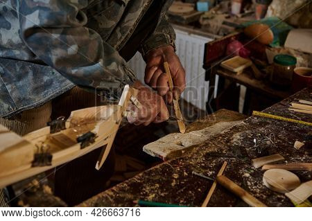 Carpenter Using Instruments To Cut Part Of Wood Material To Make Wooden Model Of Sailboat. Craftsman