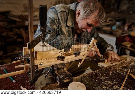 A Mature Carpenter Works On A Wooden Toy Sailboat In His Workshop. Craftsman Makes Handmade Wooden O
