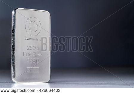 Minted Silver Bar Weighing 250 Gram Against A Blurred Dark Background.