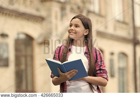Imagination And Creativity Simultaneously. Happy Child Hold Book With Pensive Look. School Education