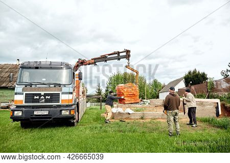 Truck With Trailer Delivered Blocks To Construction Site And Unloads A Cargo By Hydraulic Manipulato