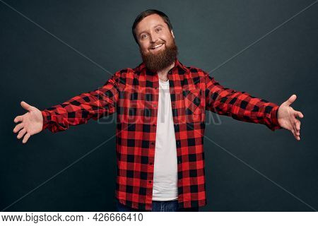 Friendly Good-looking Charming Caucasian Guy Inviting Deares Friends Come In, Spread Hands Sideways
