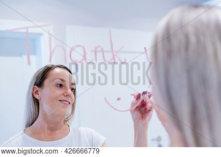 A Woman Writes The Word Thank You On The Mirror With A Lipstick.