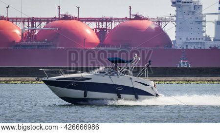 Motorboat And Lng Tanker - A Recreational Boat Goes Out To Sea