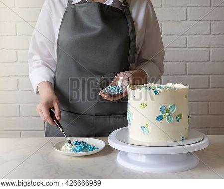 Female Baker Decorating Tasty Cake On The Table