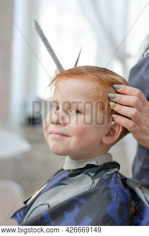 Stylish Redhead Boy At The Barbershop. Boy 4 Years Old In The Barbershop Looks At The Camera And Smi