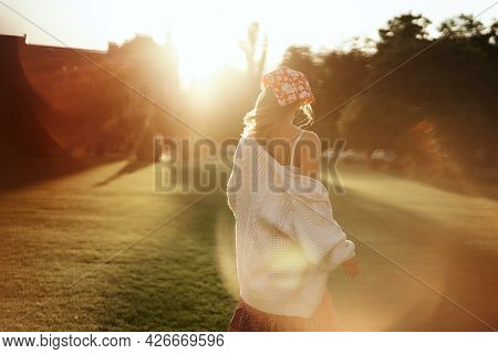 Female Runs In A Green Summer Park Out From Camera. Young Beautiful Girl In Red Dress, White Sweater