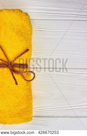Yellow Rolled Towel On White Wooden Desk Background.