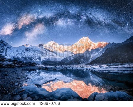 Milky Way Over Snowy Mountains And Lake At Night. Landscape