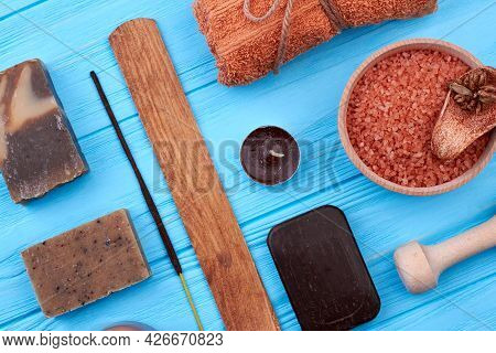 Brown Items For Spa Treatment On Blue Wooden Desk.