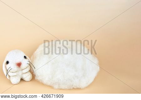 Handmade Felted Bunny Near A Piece Of Wool, Copy Space.