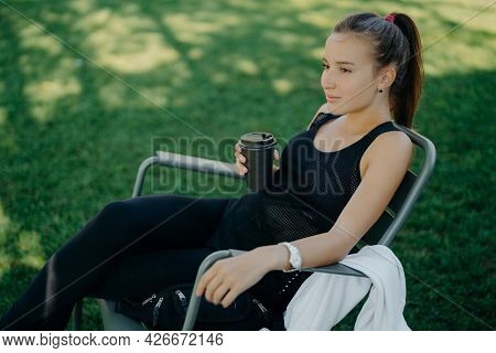 Outdoor Shot Of Thoughtful Dark Haired Beautiful Female Dressed In Sports Clothes Drinks Takeaway Co
