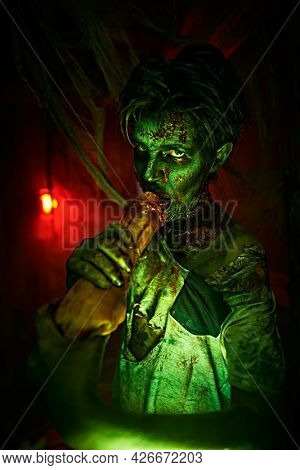 Scary zombie boy in an abandoned house in an ominous red and green light. Halloween and Horrors.