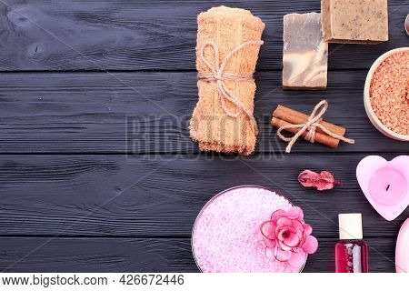 Flat Lay Spa Bathroom Accessories On Black Wooden Table.