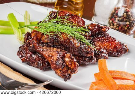 Buffalo Chicken Wings With Crunchy Vegetables On A White Plate. Close Up