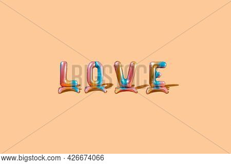 some multicolored letter-shaped balloons form the word love on a beige background with some blank space around