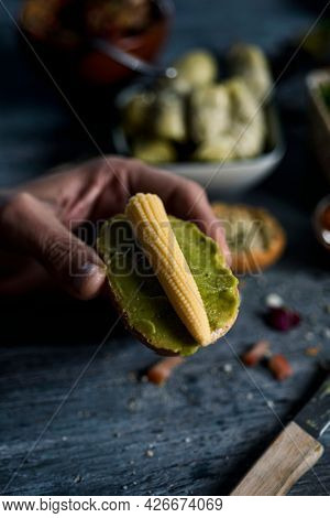 closeup of a young caucasian man having a vegan sandwich, made with guacamole and baby sweetcorn, in his hand, sitting at a gray wooden table, to a tray with some vegan appetizers