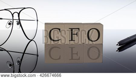 Close-up Of Cfo Chief Financial Officer Wooden Blocks On Black Background With Glasses And Pen