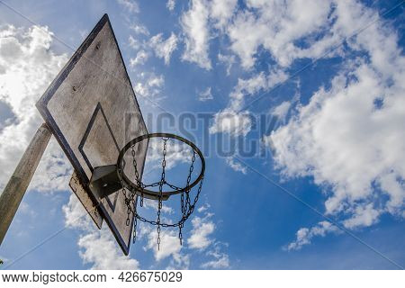 Weathered Basketball Hoop On A Sunny Day In Summertime