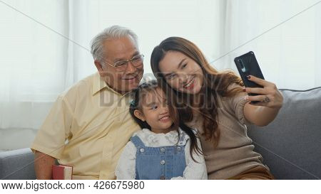Happy Family Time Relax. Asian Grandparents Laughing Taking Selfie With Granddaughter On Sofa At Hom