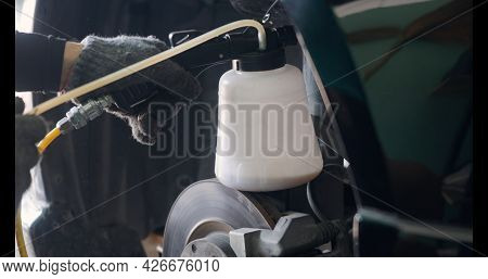 Auto Mechanic Replacing Brake Fluid On A Vehicle, Technician Bleed Air Out Of Disc Brake System In G