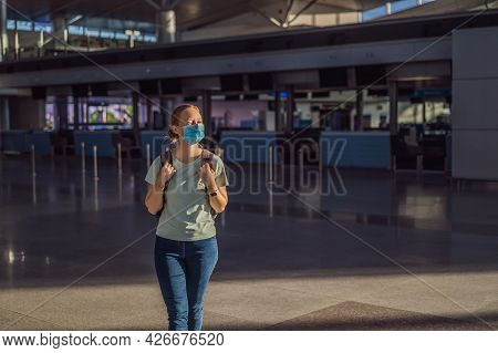 Woman In Mask At Empty Airport At Check In In Coronavirus Quarantine Isolation, Returning Home, Flig
