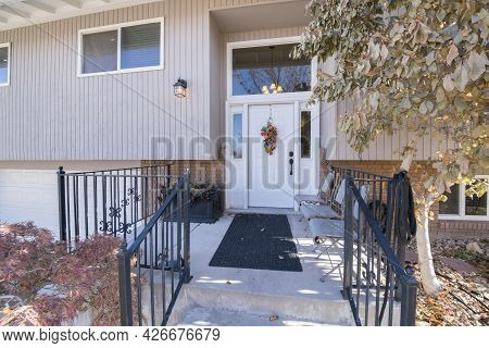Elevated Porch Of A House With Black Metal Banister