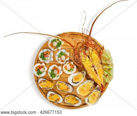 Lobster, grilled lobster stuffed with cream and cheese, grilled oysters and mussels with cheese, scallops with onion and peanuts in a luxurious serving in wooden plate with lime. Isolated on white