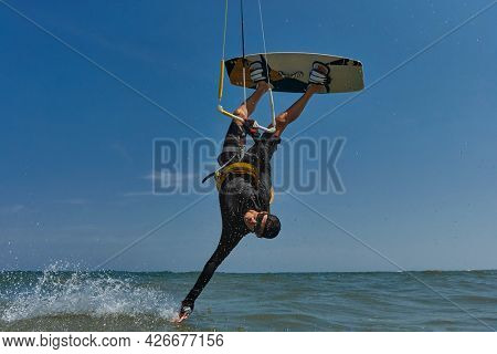 Kite surfer jumps with kiteboard  and doing