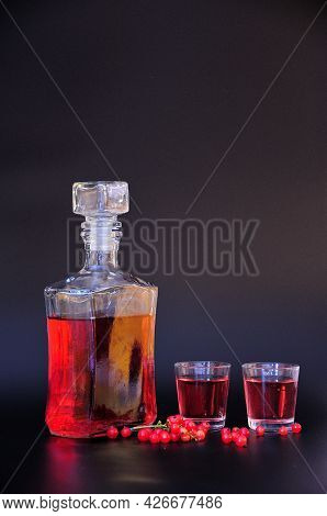 Homemade Red Currant Liqueur, In A Glass Bottle And Two Glasses, Next To A Branch Of Fresh Berries O