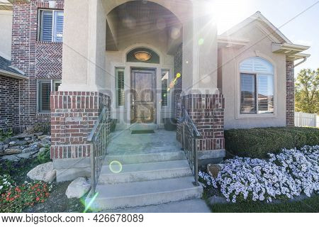 House Building Exterior With Bricks And Front Yard Flower Garden